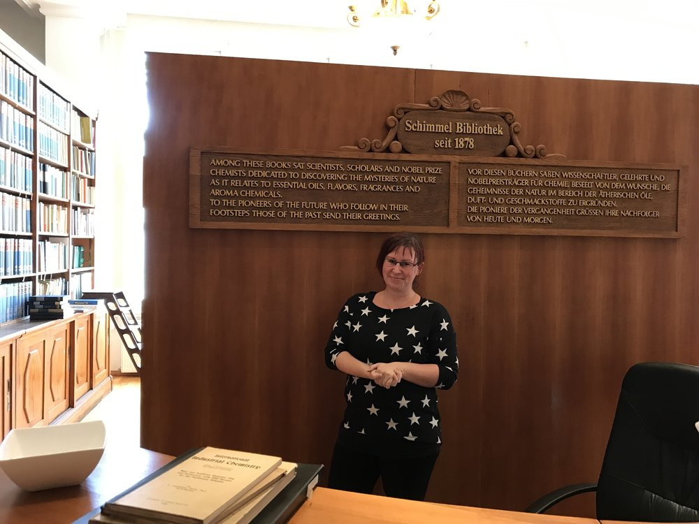 "Schimmel Library front desk, with librarian Ricarda Bergmann, a real star. The inscription above her head reads: ""Among these books sat scientists, scholars and Nobel prize chemists dedicated to discovering the mysteries of nature as it relates to essential oils, flavors, fragrances, and aroma chemicals. To the pioneers of the future who follow in their footsteps those of the past send their greetings."""