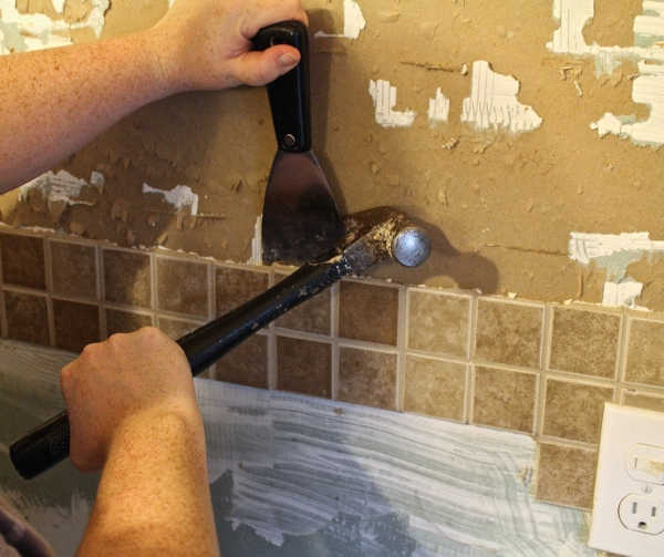 it is very important that you use a putty knife that is labeled stiff this will give you leverage to remove the tile and the metal knife wont bend - Removing Tile Backsplash
