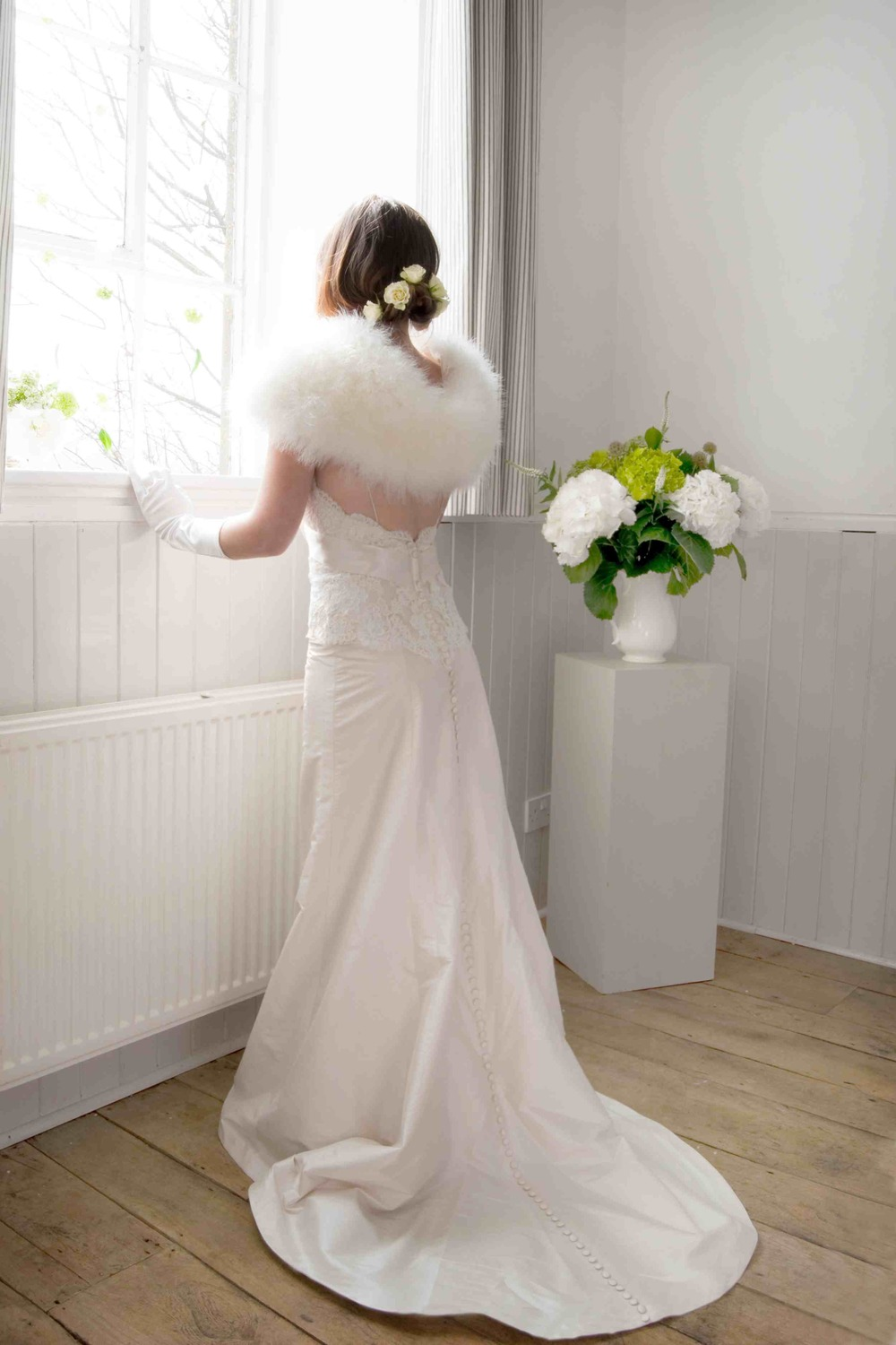 A gorgeous ivory dress with faux fur stole and long white evening gloves. Dress by Village Brides Photo by Cristina Colli