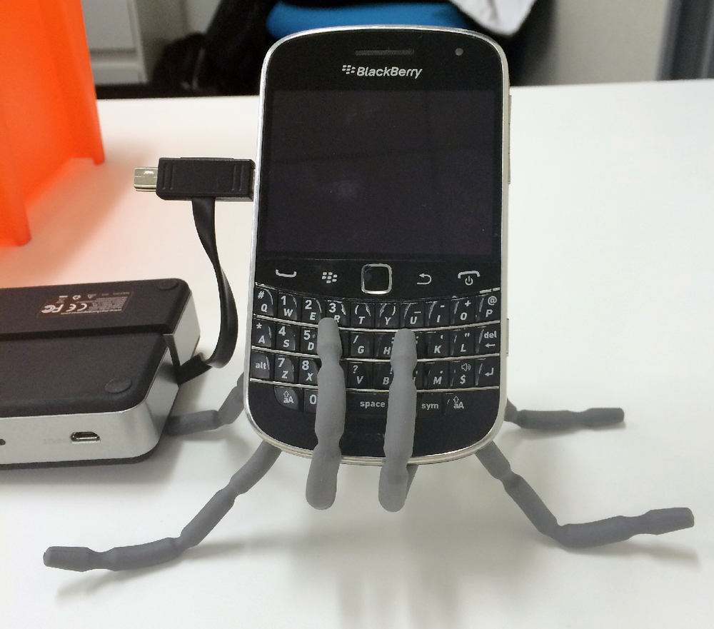 Holding up a blackberry while it is being charged by an external battery