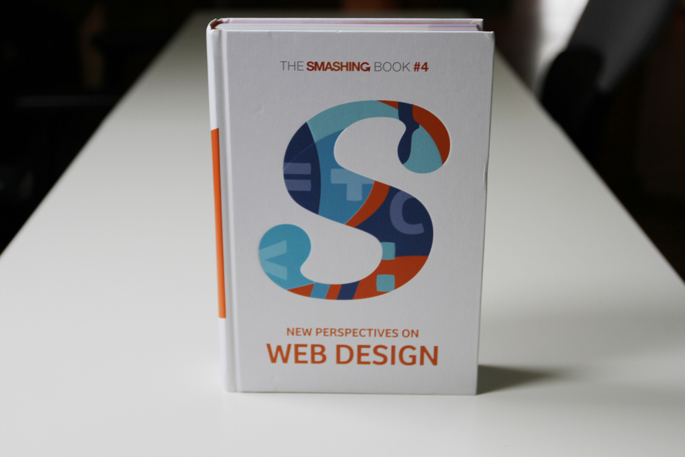 "The front cover for the new book features the Smashing ""S"" filled with code symbols highlighting this edition's theme."