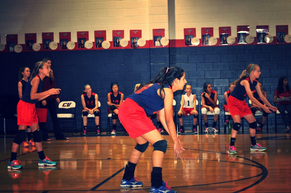 8th graders Ally K., Krishna V., and Caroline G. get in place to receive a serve. Photo by Sanika