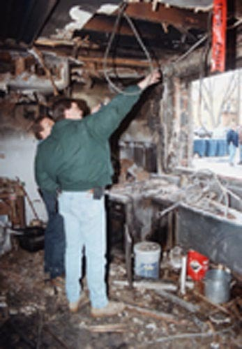 Randy Putt (left) of Putt Refrigeration and Heating and Pat Springer of Centre Region Code inspect fire damage in the kitchen at the Theta Chi fraternity house on South Allen Street. Cr: Mike Morones