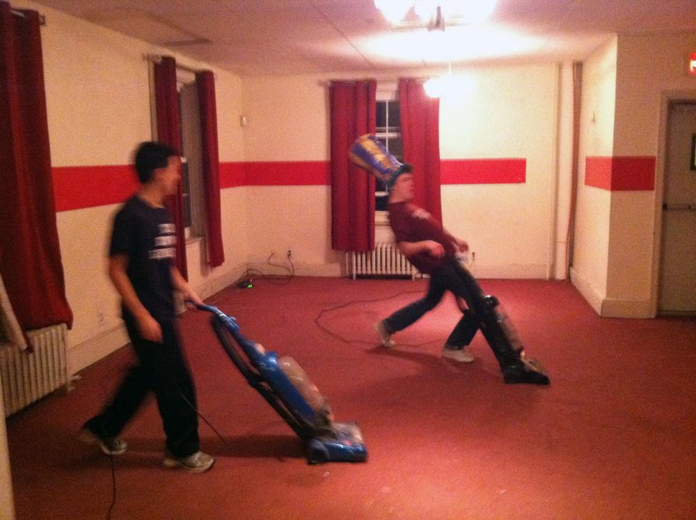 2013 Alumni Work Weekend - Pool Room Project Matt Liu (L) and Zach Kramer vacuum the New Carpet