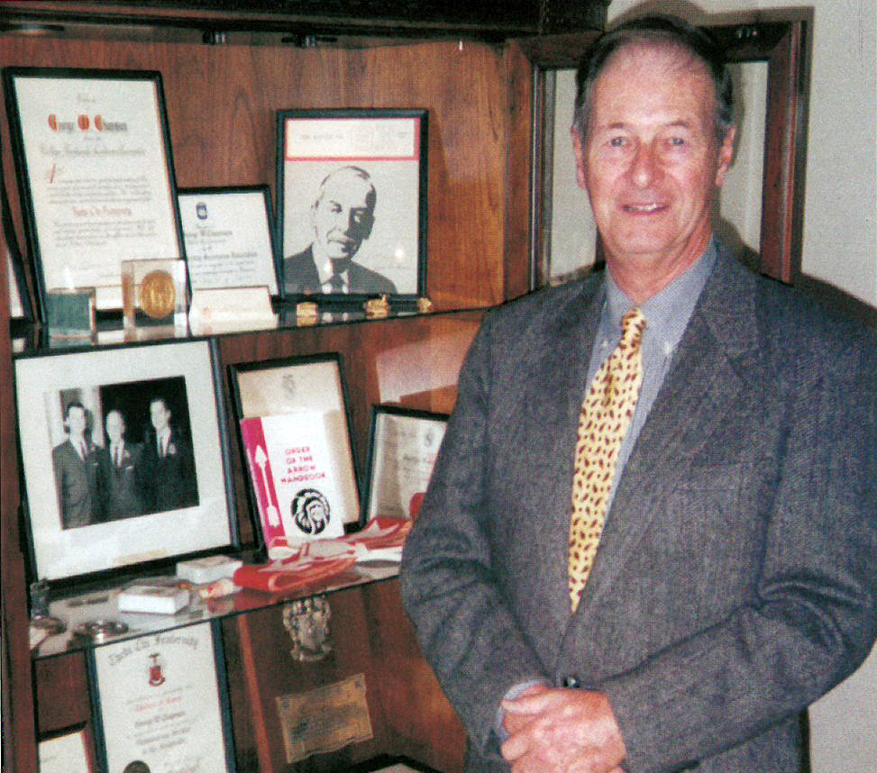 George W. Chapman Jr. (Omega/Penn State '49) stands before a display case at the International Headquarters in which are displayed many mementos and personal artifacts of his father, George W. Chapman (Omega/Penn State '32)