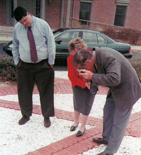While photographing his brick, and the adjacent bricks in the Pathway of Brotherhood upon which are engraved the names of his brother (Philip C. Chapman, Omega/Penn State '57) and father (George W. Chapman, Omega '32), Brother Chapman and his wife, Marion, are assist-ed by Scott Thomas (Delta Kappa/Ball State '97), Director of Chapter Services