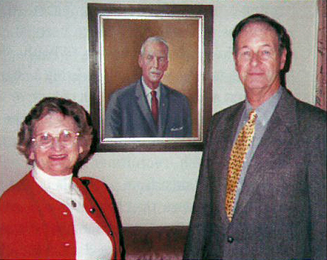 Marion and George W. Chapman Jr. stand before a portrait of George W. Chapman that hangs on the wall of The Chapman Library at the International Headquarters