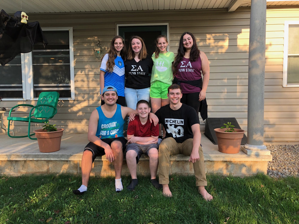 Tim Gregory (L), AJ Bobby, OX THON Child and Patrick O'Brien (R) with in back row with AJ's sisters, Annabelle (Blue) and Alexis (Green), and members of OX partner organization Sigma Alpha