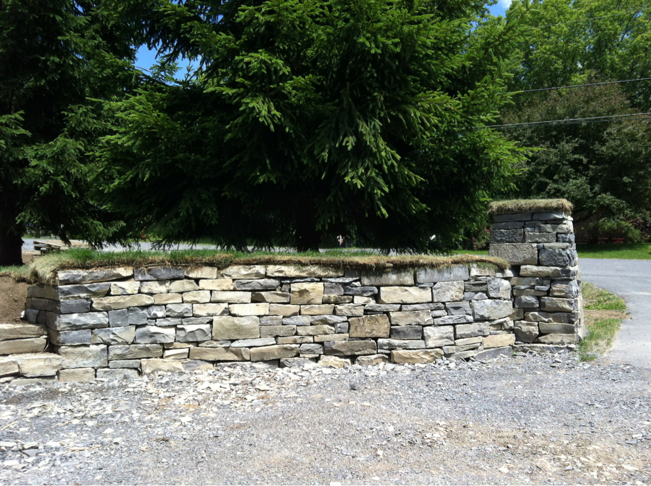 This dry stone retaining wall was constructed in reclaimed Kingston Limestone. The stone had previously been used in a mortared wall on the shores of Lake Ontario that was slated for demolition.     The wall ties in to a 4' gatepost that is mirrored with a matching gatepost on the opposite side of the driveway.    Both the wall and posts is capped with a layer of turf in the place of traditional coping stones.    Edgewater Stonemasons is a member of Dry Stone Walling Across Canada, and designs and builds dry stone projects in a wide range of stone types.
