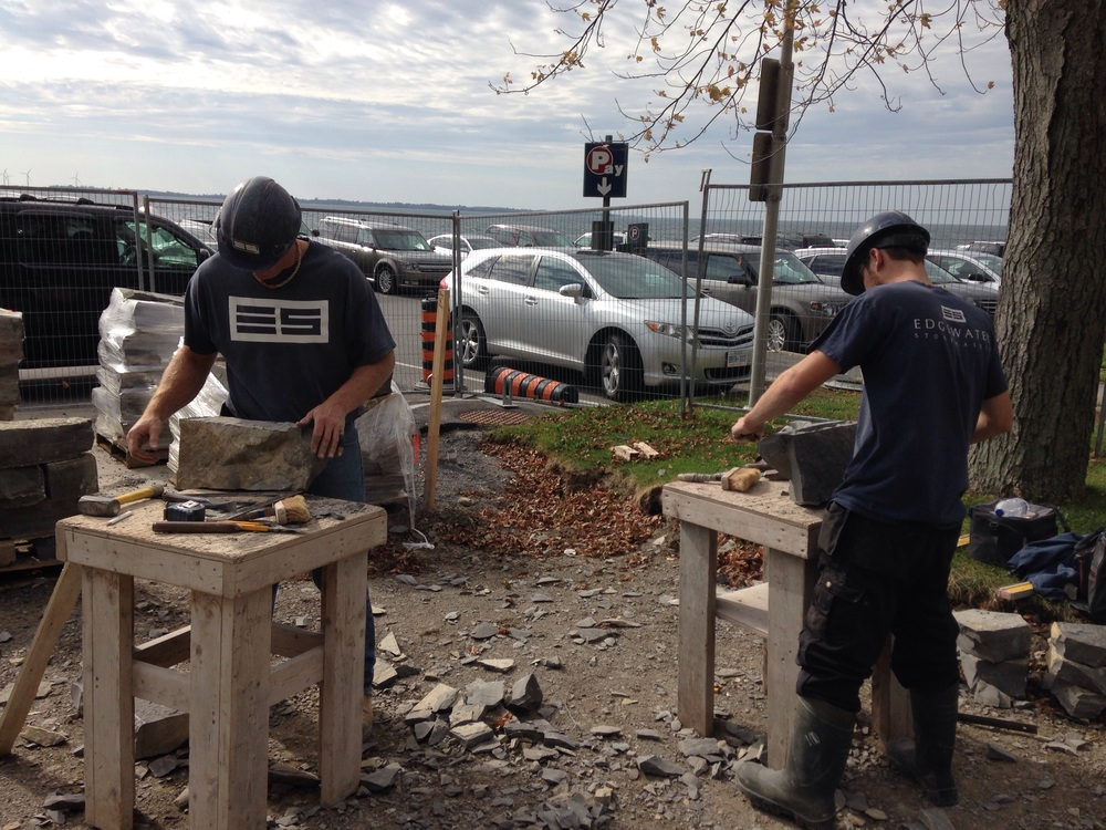 Stonemasons preparing blocks of Limestone for use in a natural stone retaining wall. Kingston, ON