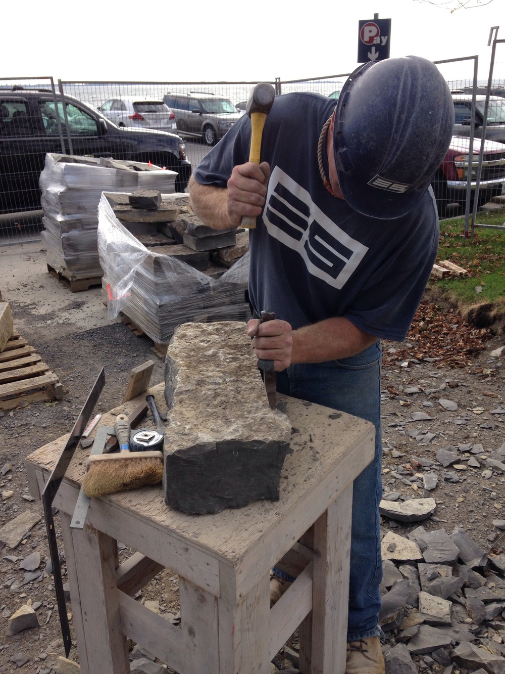 A piece of Kingston Limestone is squared using hand tools. The perimeter of the stone is marked, and excess material is 'pitched' away to ensure all sides are square.