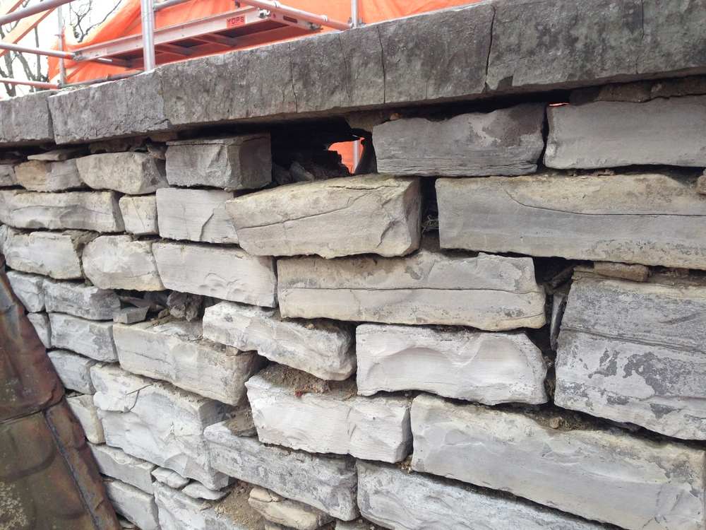 Dislodged stones, a result of moisture accumulation within the wall and resulting freeze-thaw movement.