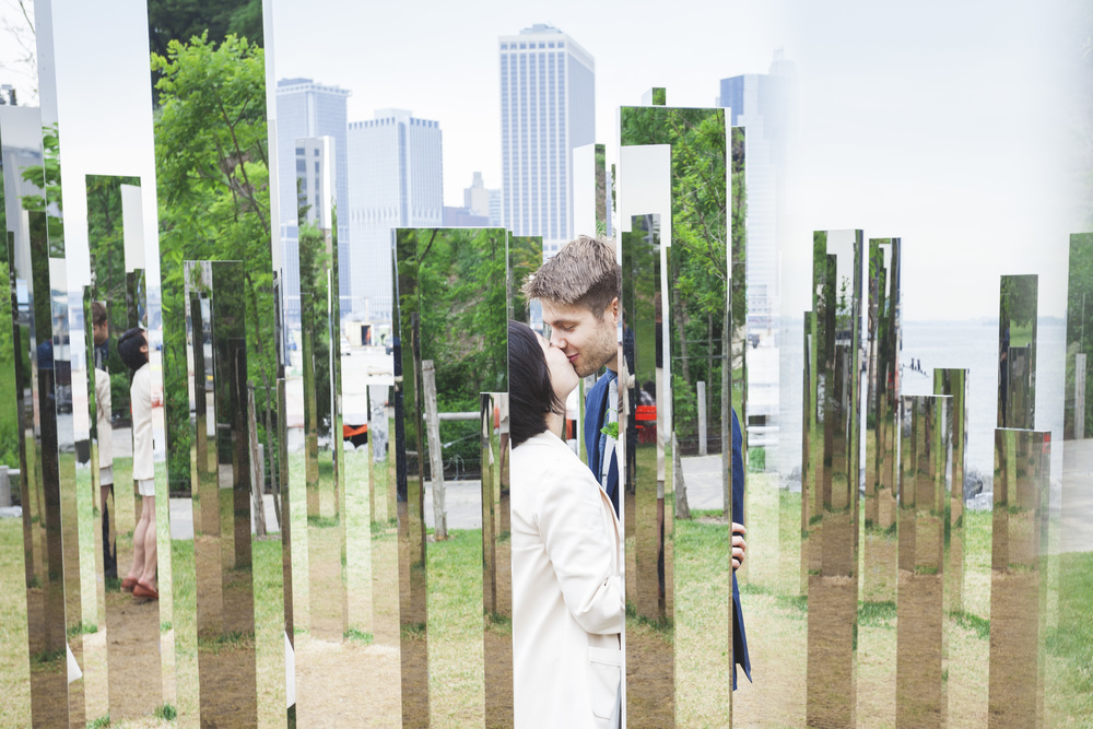 A very cool mirrored art piece along the river in NYC makes for a unique wedding couple shot.