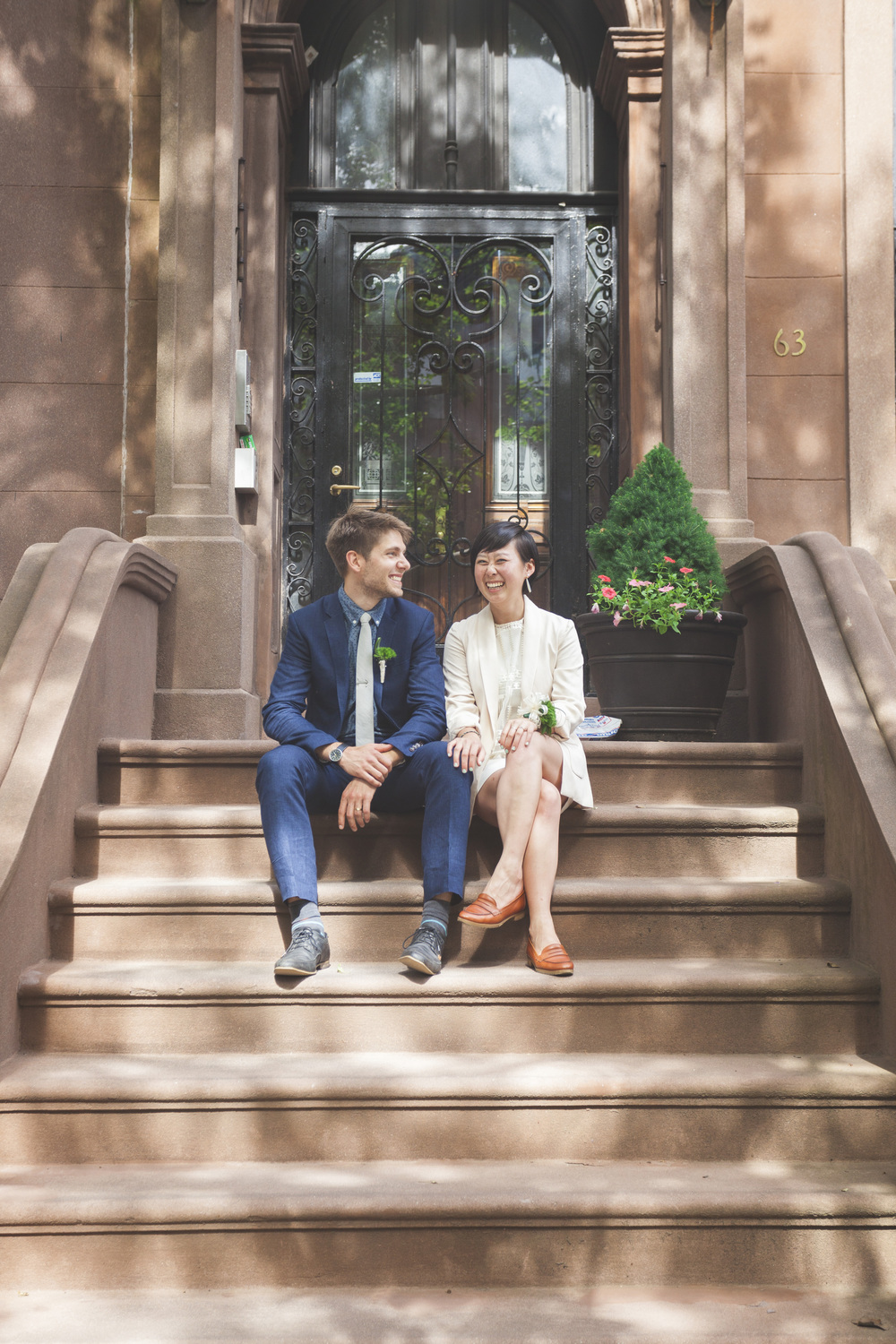 The happy couple outside a classic brownstone on their former street.