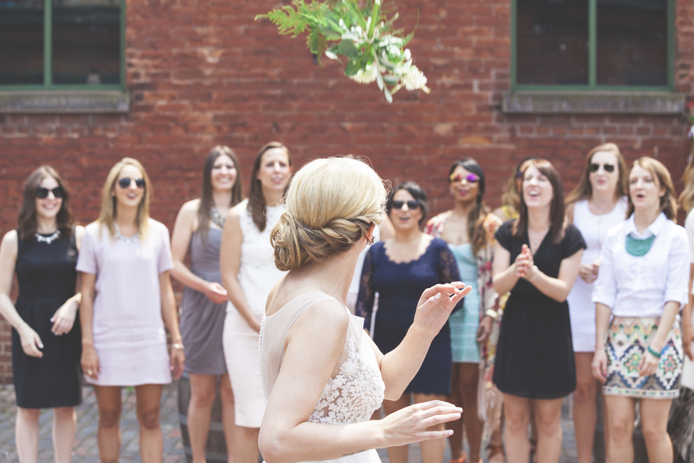 The bouquet toss with a look back from the bride.