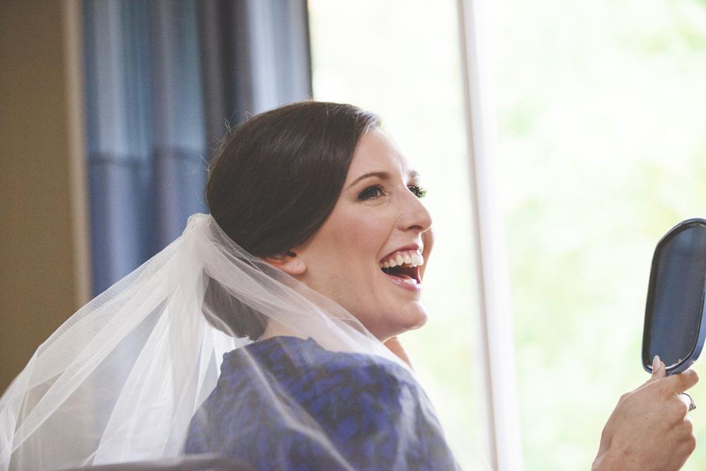 The bride admiring the MUA work.