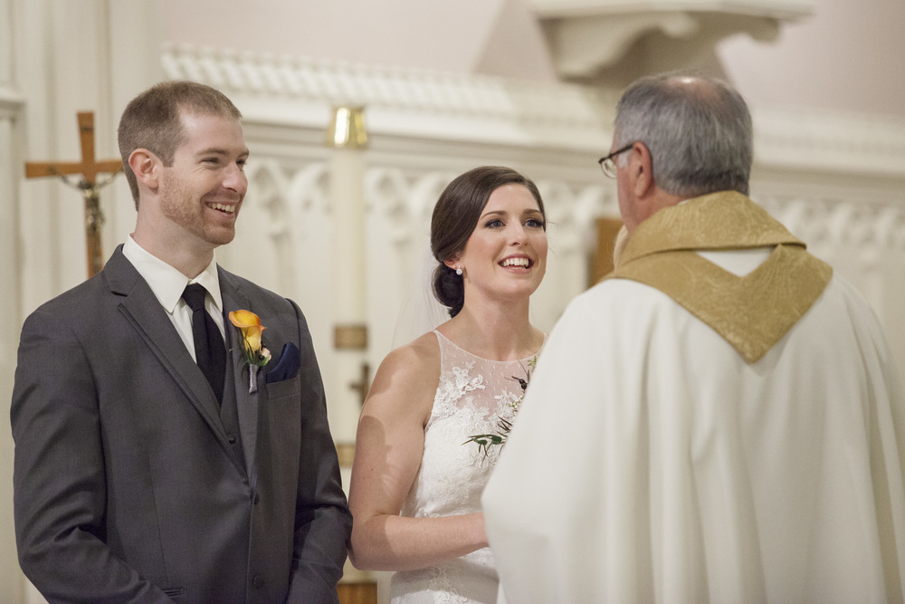 The bride and groom having a quick pep talk with the priest.