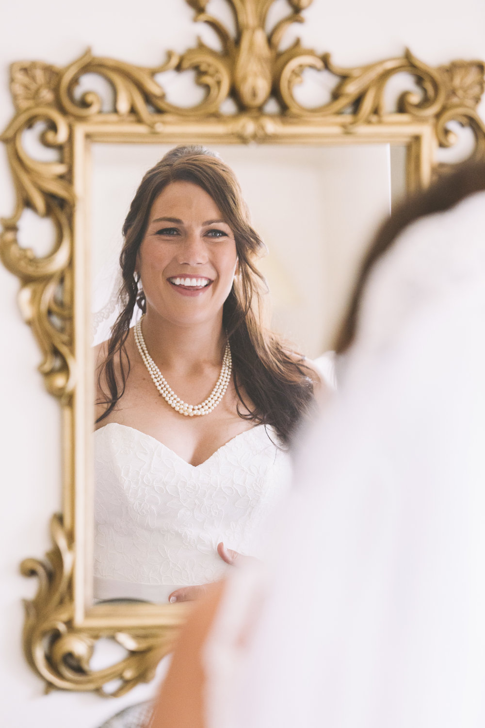 bride staring into mirror on her wedding day