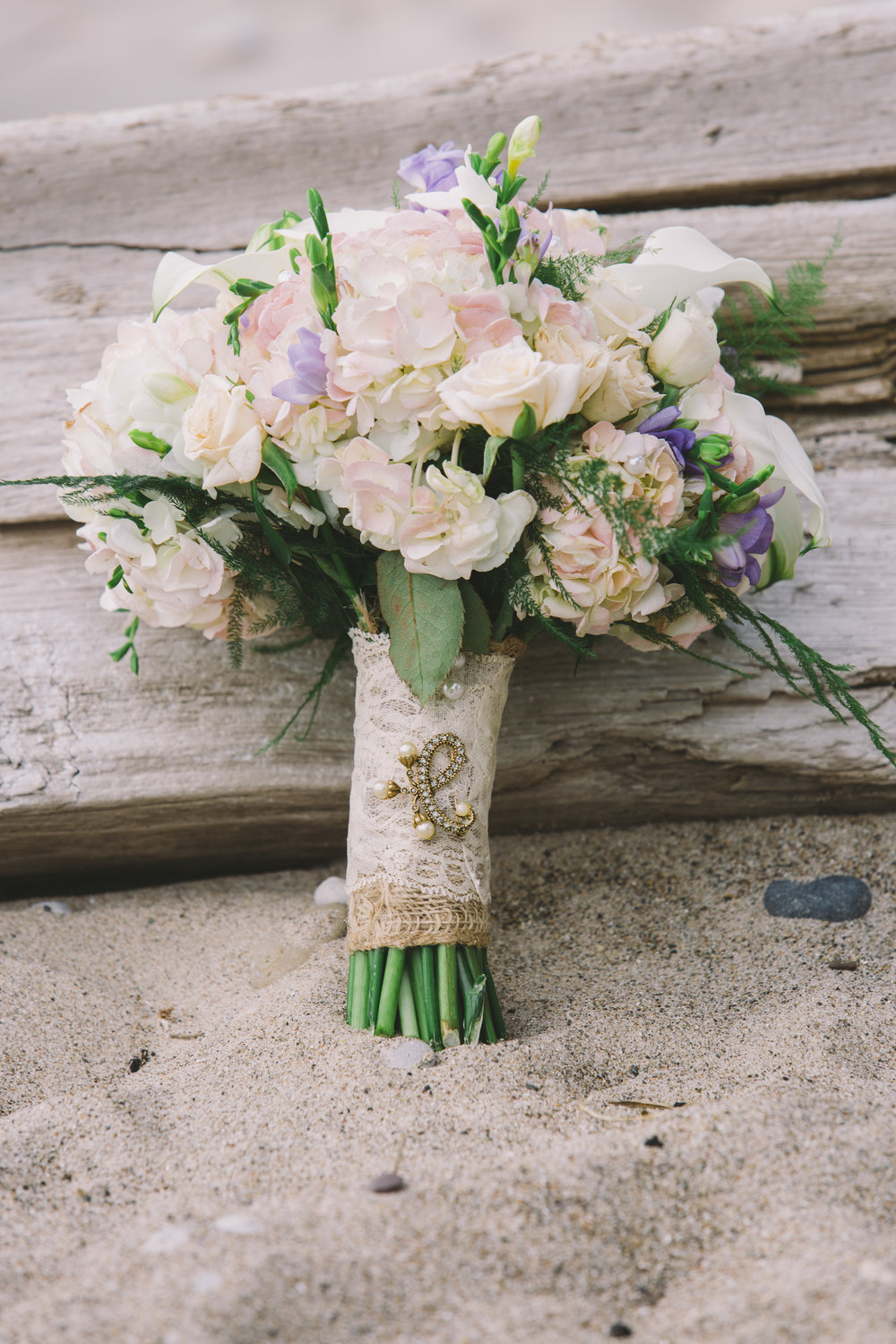 Wedding bouquet of flowers leaning on beach driftwood