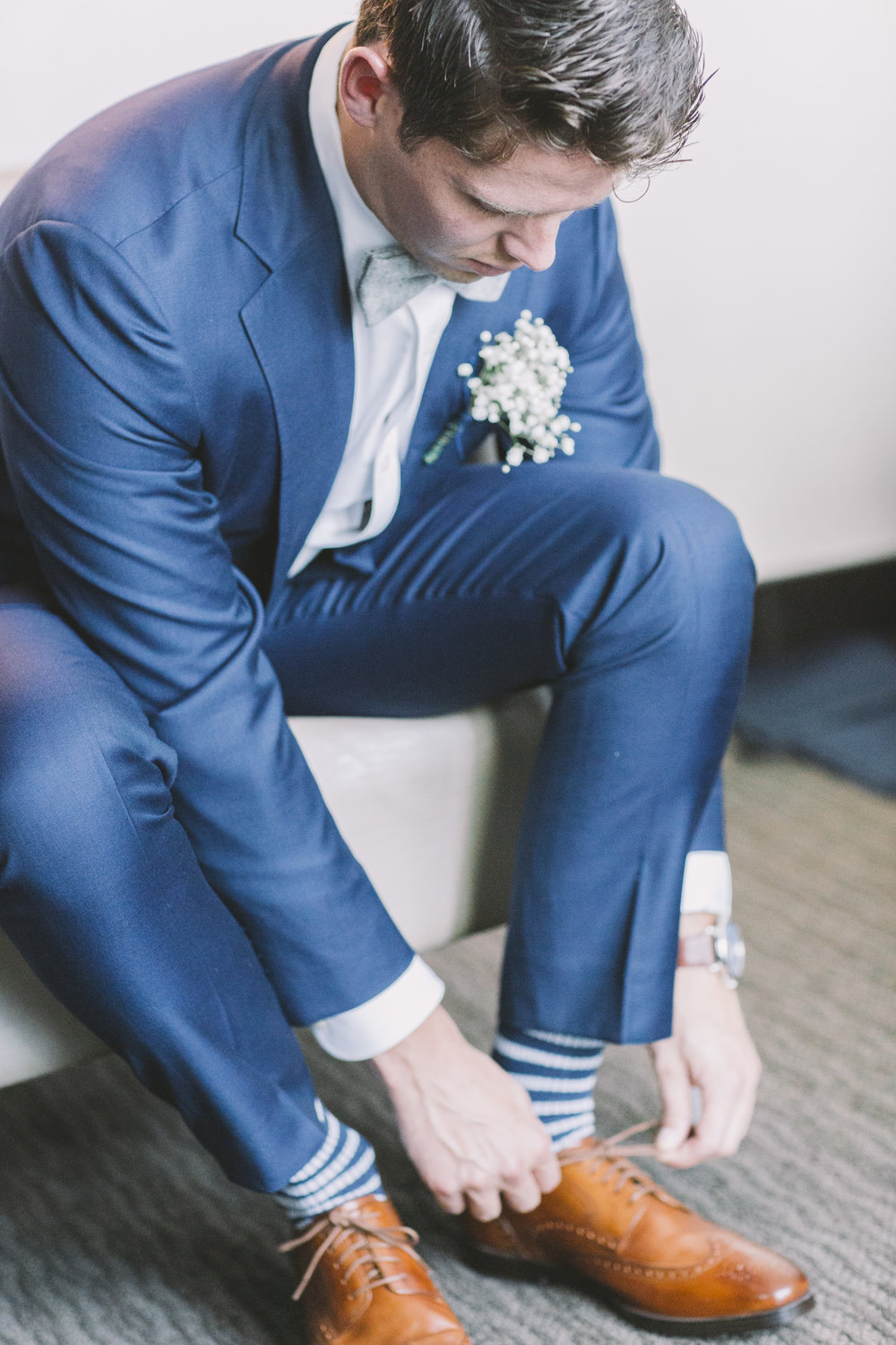 Groom lacing up dress shoes.