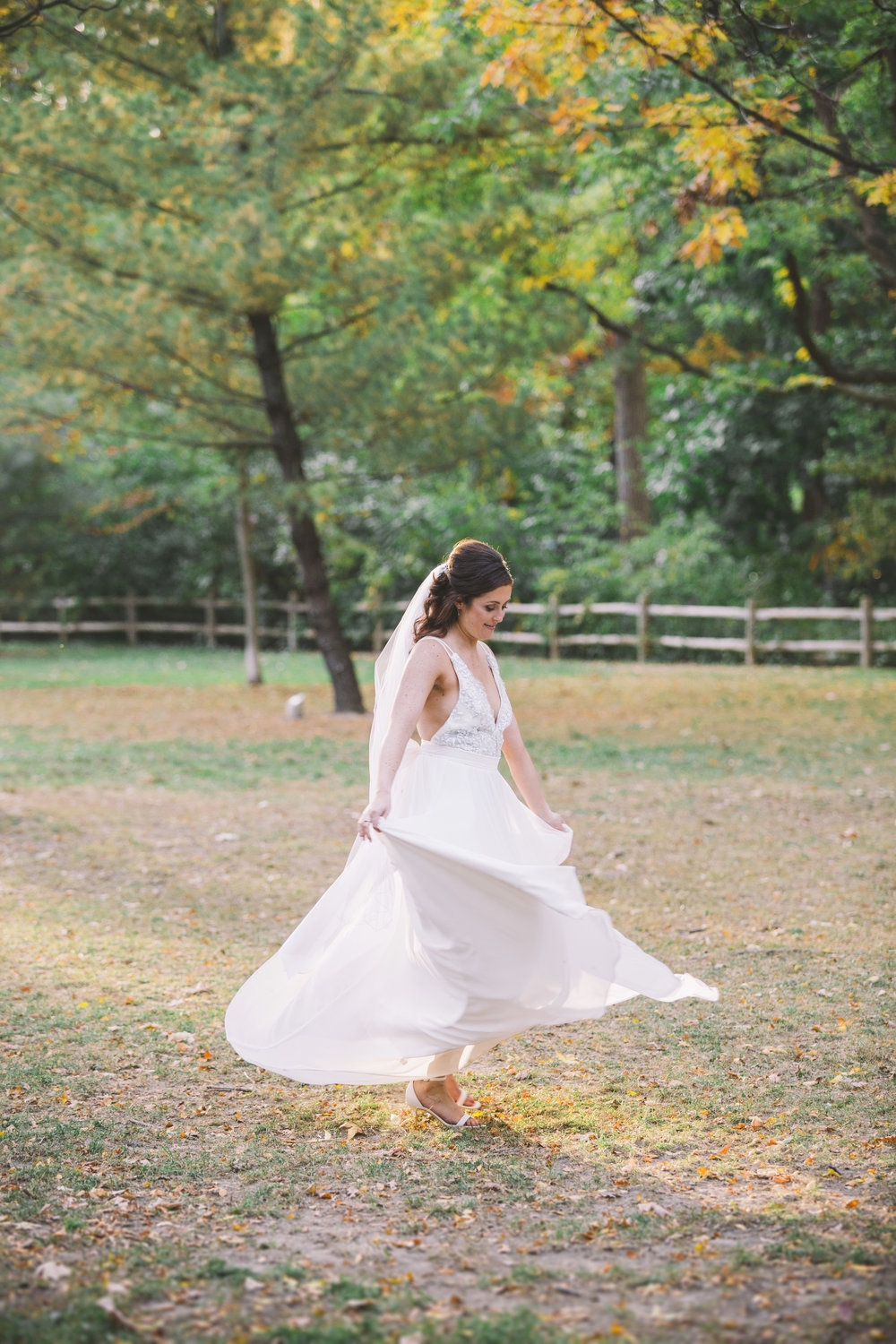 Bride twirling in wedding dress in the fall.