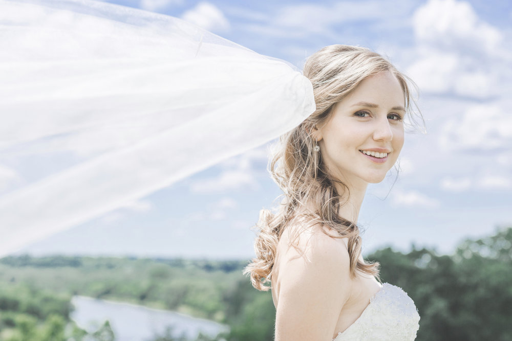 Bride with flowing veil photographed by the Grand River in Brantford Ontario.