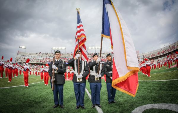 Kevin holding presenting the American Flag at half during of a U of H game.