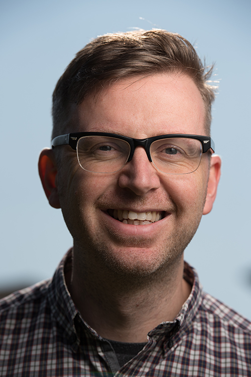 Simon Dixey smiling with glasses and a plaid shirt on