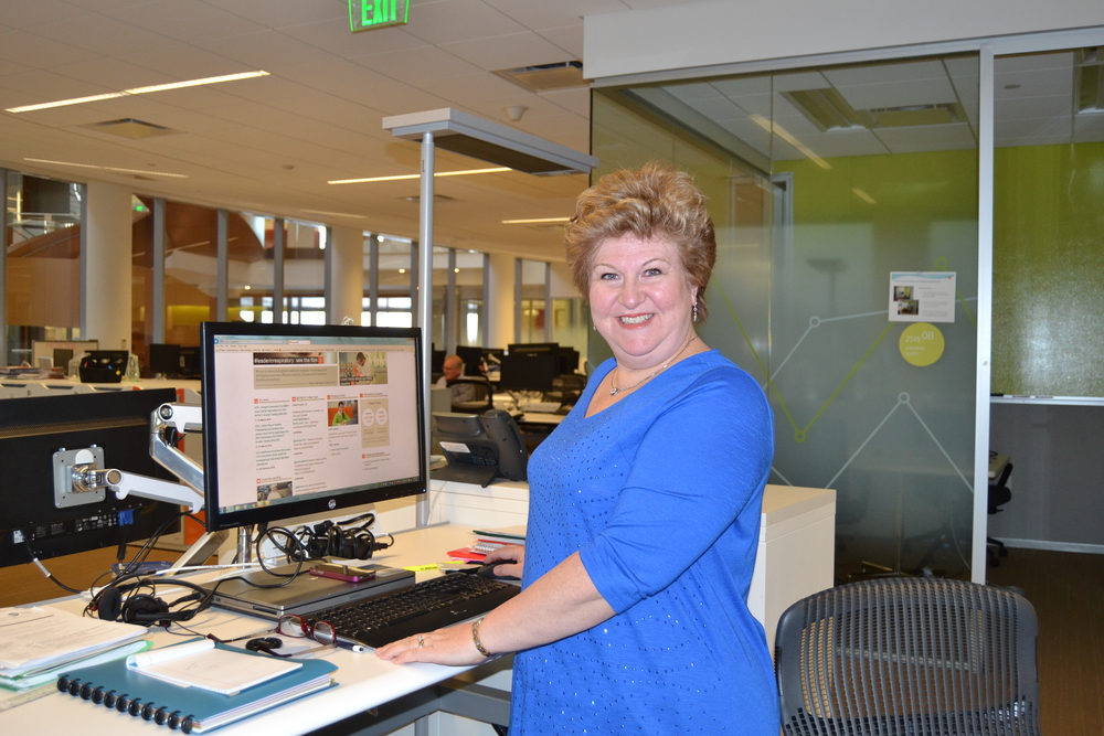 """Linda at sit-stand workstation, part of GSK's healthy workplace design, March 2016."""