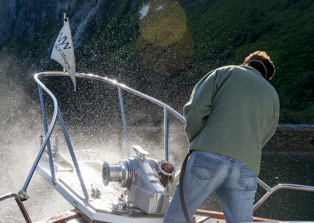 Karen, the master of the windless, cleans the anchor chain as she brings it on board