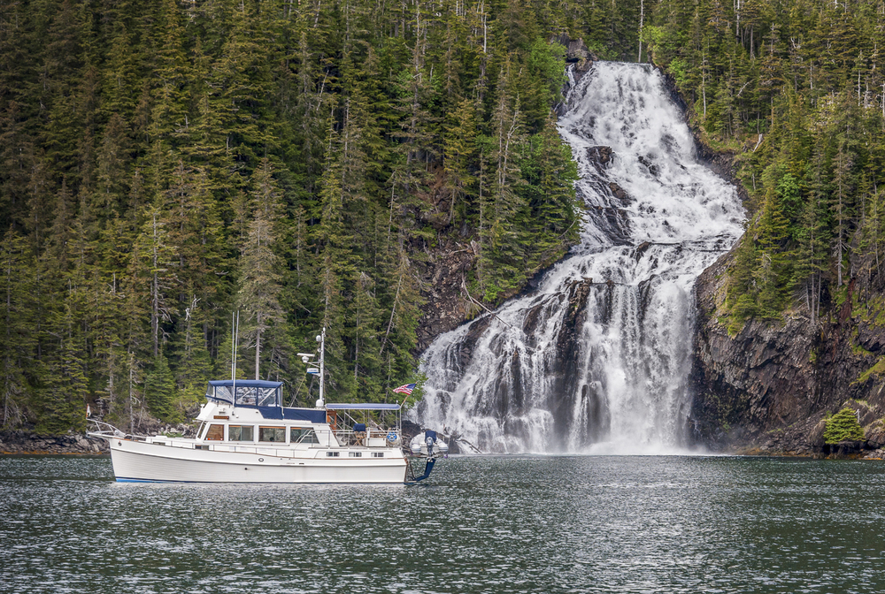 Telita  passes in front of the waterfall in Cascade Bay