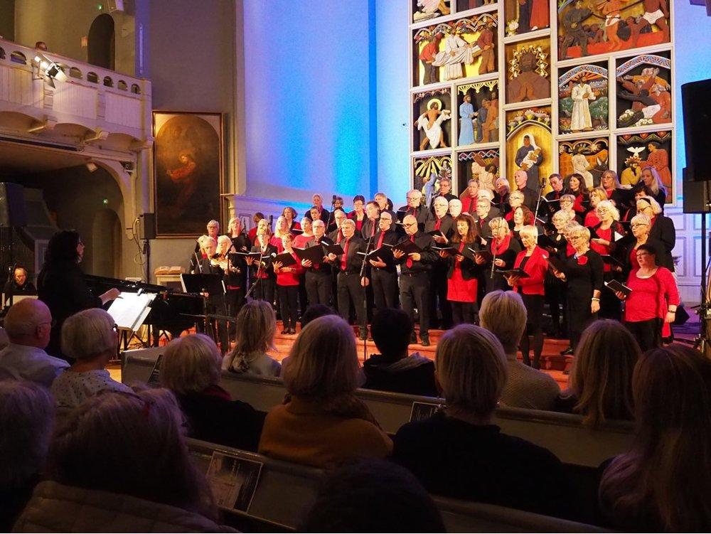 """Koret i full gang. Dirigent Kristin Ellefsen """"ute til venstre"""", og Gunnar Johan Hansen på keyboard i bakgrunnen.  Julian Saxl ser vi på fiolin foran """"venstre hjørne av koret"""""""