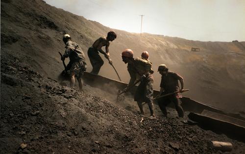 Beb C. Reynol; Workers shovel coal dust Karkar, Afghanistan