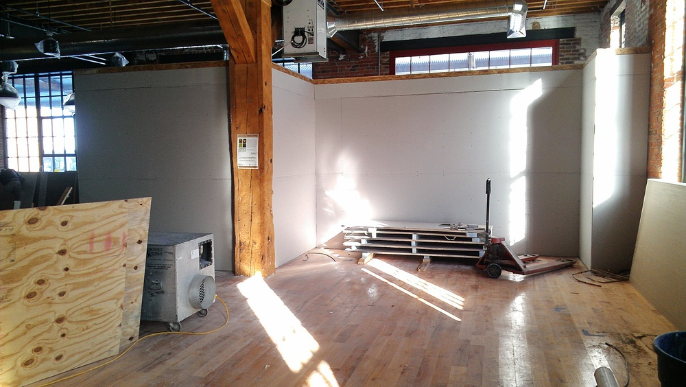 This picture was taken standing at the south end of the store facing east. To the left of the amazing wooden beam is our front end office, and to the right is an alcove into which one of our freezer cases will be placed. On the other side of the wall is our seating area.