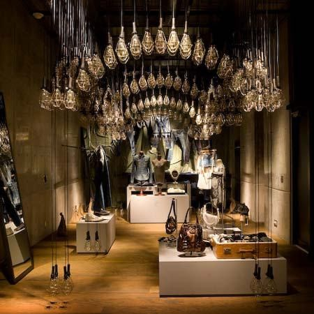 In this Diesel store, low ambient light, accent lighting and decorative lighting are combined to create a treasure-trove feel to this display.