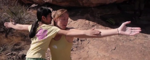 Ashima comparing wingspan with an adult pro climber in Hueco Tanks.