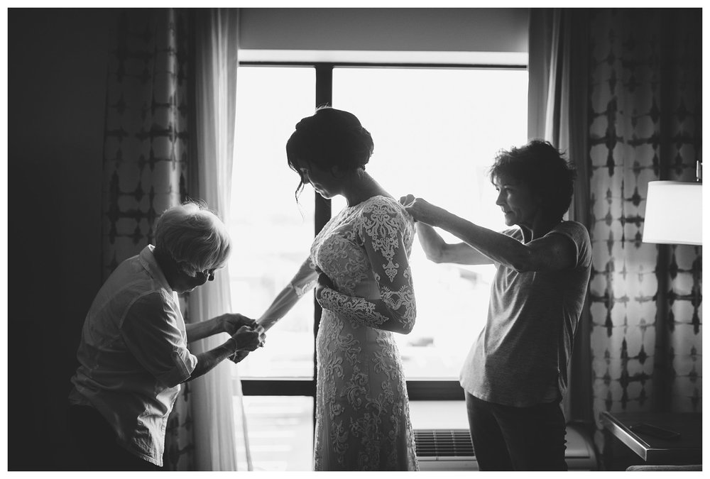 Jamie with her mother and soon to be mother-in-law helping button her dress. Such a sweet moment.