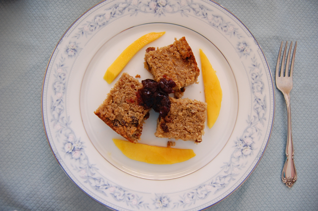 Organic baked oatmeal bars topped with jelly with a side of organic mango slices on Noritake fine china dishes
