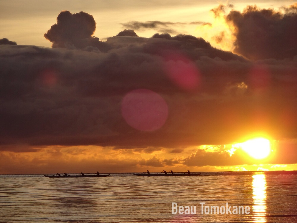 This is a beautiful sunset photo where the beams are on the ocean and a pair of canoes passing by on a beautiful Saipan beach.  The photography was by our brother Beau Tomokane.
