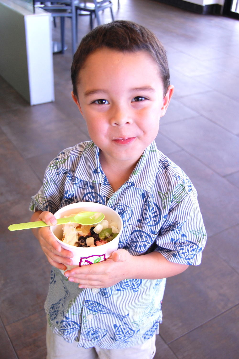 Abraham smiles as he enjoys eating his dessert from Guam's Yogurtland