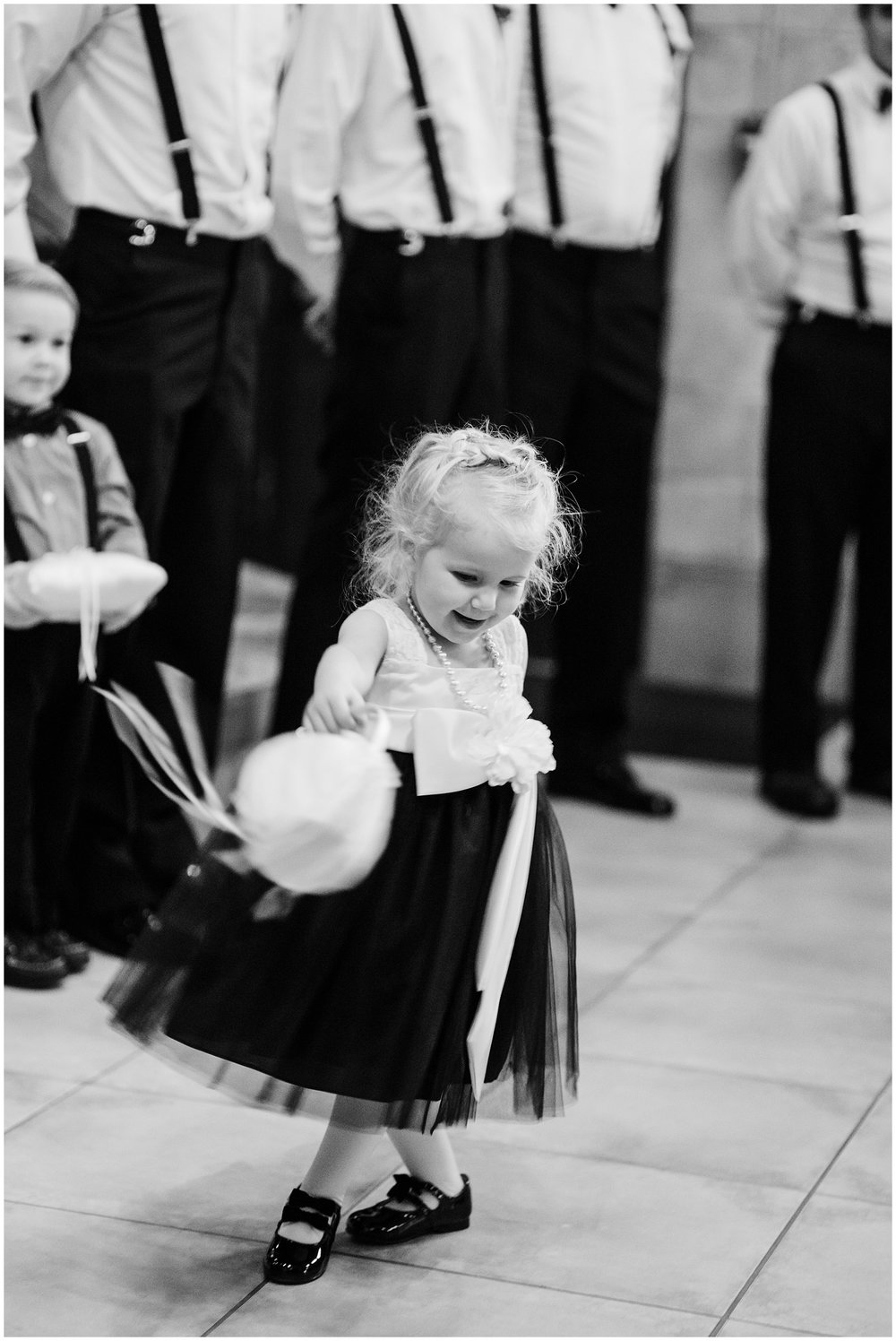 Is there anything more delightful than an adorable flower girl lost in her own little world?