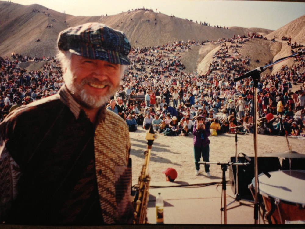 In 1994 the Consort had an incredible performance on a stage in the Negev Desert of Israel. This is a shot of Paul Winter with the throngs of fans watching the show from the sand dunes.