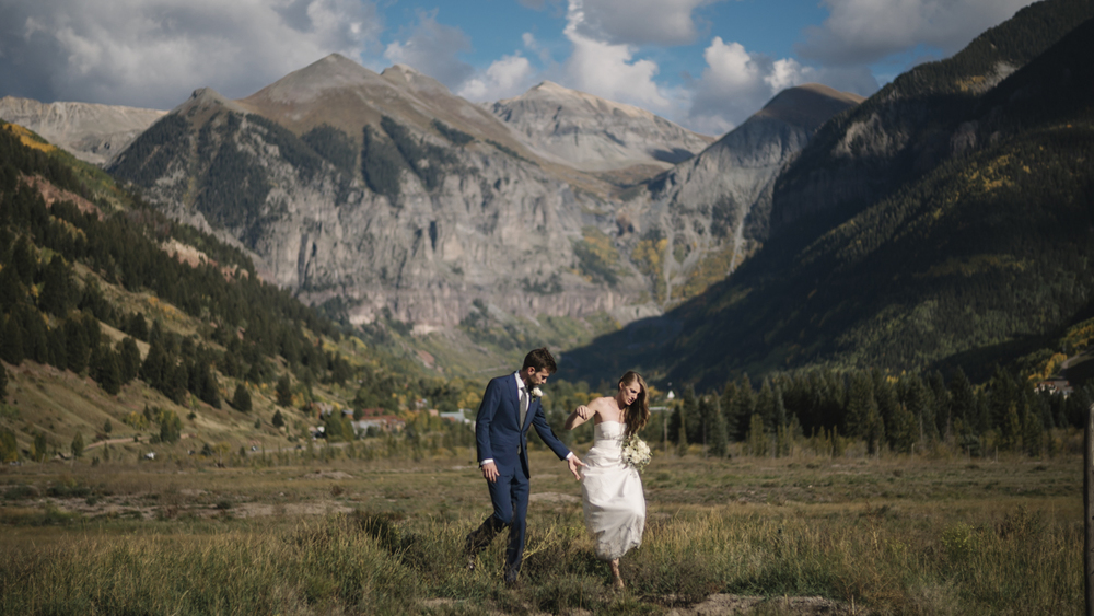 Bride And Groom Walking Through a Field in Telluride.