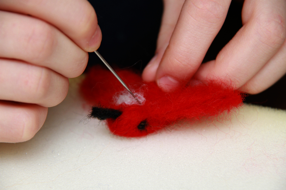This student is carefully using a barbed needle to sculpt this beautiful bird out of un-spun wool.