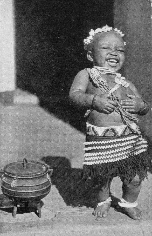 blackhistoryalbum: Child laughing next to a three leg cooking pot. South Africa. | Scanned old postcard. ca. 1940s