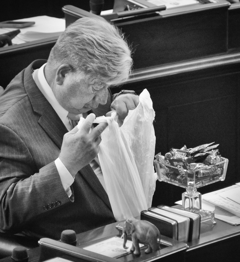 Sen. Bill Cook checks his candy stash at the conclusion of the legislative session on August 28, 2017.