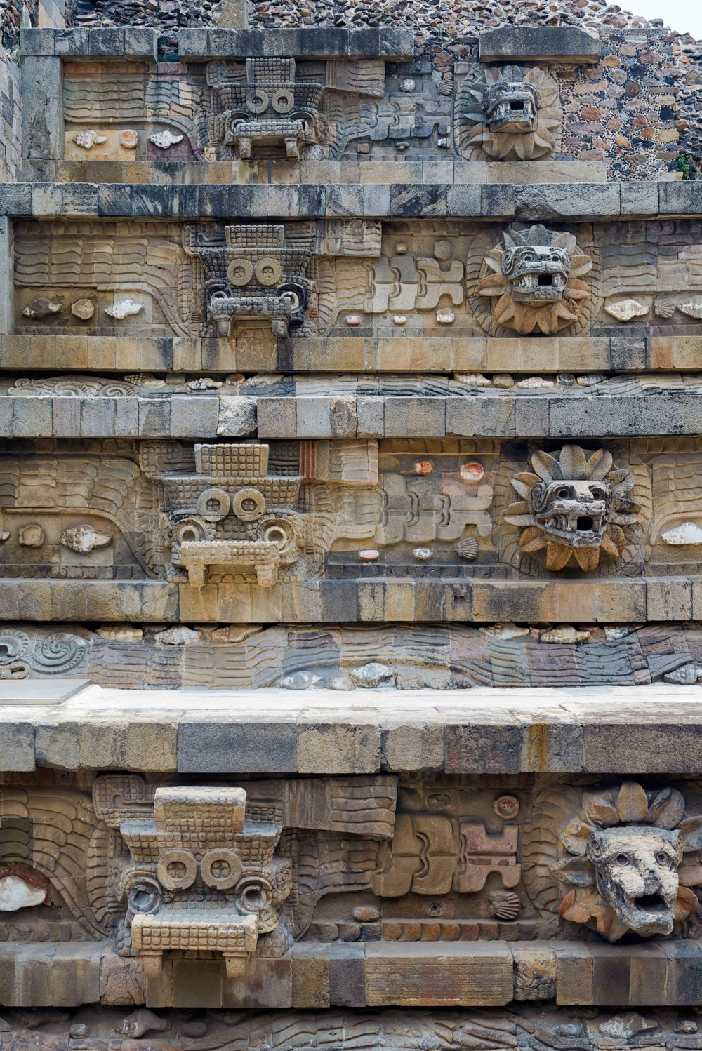 Under each row of heads are  bas-reliefs  of the full feathered serpent, in profile, also associated with water symbols.