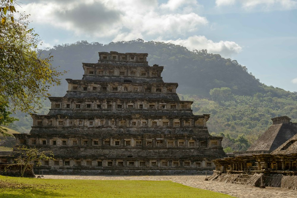 "The pyramid has seven stories. Each of these consists of a sloping base wall called a talud and a vertical wall called a   tablero  , which was fairly common in Mesoamerica. What is unusual about this construction and others in the city are the addition of decorative niches with the top capped by what Jose Garcia Payon called a ""flying   cornice  ,"" a triangular overhang."