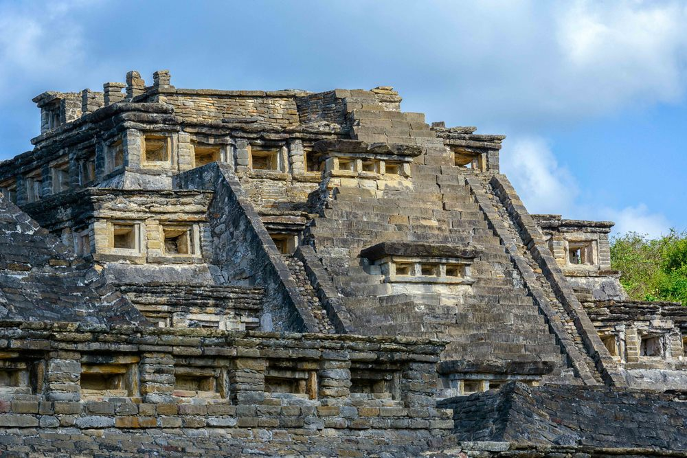 The stairway to the temple of the Pyramid of the Niches is adorned on the sides with frets, which are called Xicalcoliuhqui. It is thought to symbolize lightning and while it is common in Mesoamerica, it is a very prominent motif here. These frets were probably painted blue as they were on other buildings, where remains of paint have been found. At the top of the stairway were probably two large three-dimensional stelae.