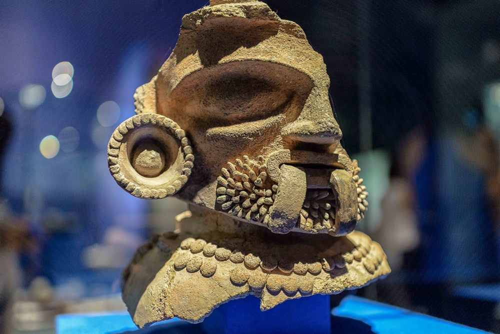 Anthropomorphic brazier in which we can see a portion of the face of a bearded person with the lips parted, out of which comes a bifurcated tongue.It wears a circular ear spool decorated with small, round appliqués on the edge. It also wears a two-stranded necklace of spherical beads.